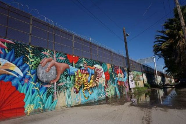 Képeket fest az Egyesült Államok és Mexikó közötti falra egy mexikói művész